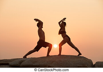 Couple are engaged in fitness yoga exercise on the stone in...