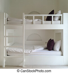 Clean hotel room with wooden bunk beds. Vintage effect style pictures.