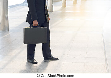 Businessman pulling a bag in a big city.