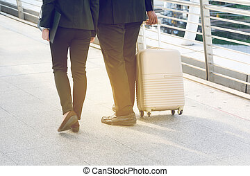 Businessman and Businesswoman pulling a suitcase in a big city.