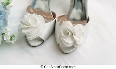 Wedding bouquet and bridal shoes on white background