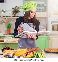Pretty young female cook wearing Chef s hat looking for a...