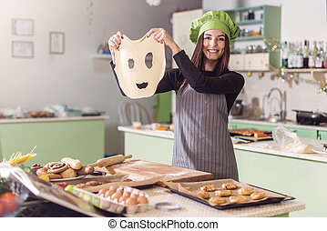 Young housewife having fun holding funny dough face while...