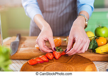 Close-up view of female hands putting sliced strawberry on a cake layer. Woman making berry pie in the kitchen