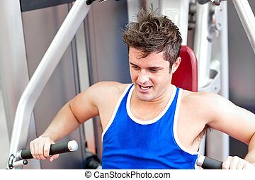Muscular man using a bench press in a fitness center
