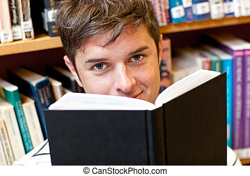 Attractive man looking behind his book in the library