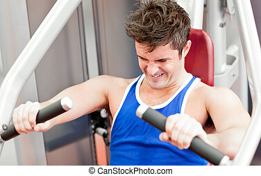 Strong athletic man using a bench press in a fitness center