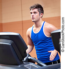 Concentrated athletic man training on a running machine in a...