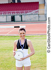 Smiling female athlete with a gold medal holding a disc