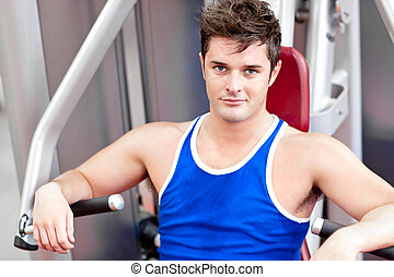 Self-assured young man using a bench press in a fitness...