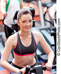 Smiling athletic young woman standing on a running machine