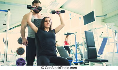 Trainer helps young strong brunette woman doing exercise in fitness club and gym center