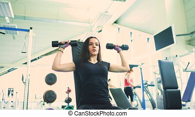 Strong brunette woman doing exercise in fitness club indoors