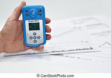 Mans hand with Oxygen meter. Abstract photo with documents.