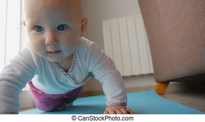 Baby with blue eyes trying to crawl on floor