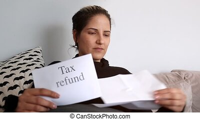 Woman receives tax refund - Woman holds envelope and reading...
