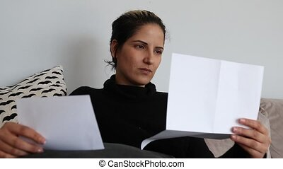 Sad and shocked woman reading a letter on a couch