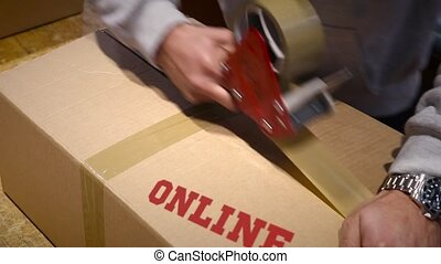 Shipment of online items - Production worker sealing carton...