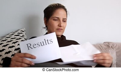 Woman sitting on couch reading results letter - Woman holds...