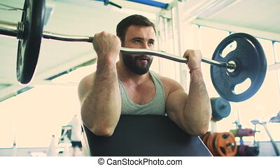 Handsome sporty man is exercising in fitness club and gym center
