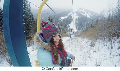 Girl on lift winter - On fifth lift rides smiling girl