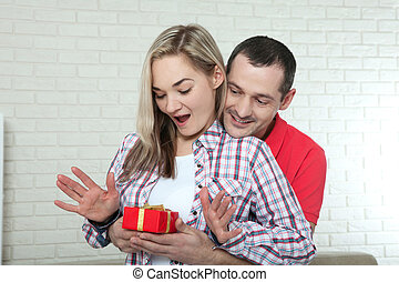 valentine's day or christmas concept - young woman opening gift