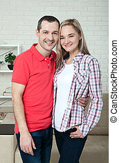 Happy young couple smiling. Man and woman hugging at home.