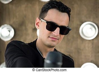 Male singer in sunglasses with microphone performs in...