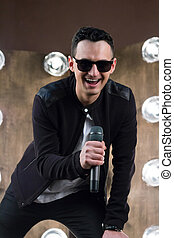 Male singer in sunglasses with microphone singing in...
