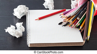 Pencils on Notebook - Colour pencils and notebook on a black...