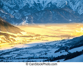Morning in alpine valley. Winter haze illuminated by ray of...