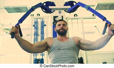 Handsome sporty man is exercising in fitness club and gym...