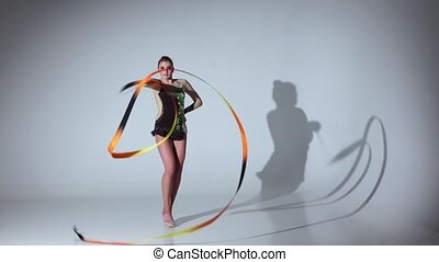 Gymnast gracefully move with a ribbon in his hands. White background. Slow motion