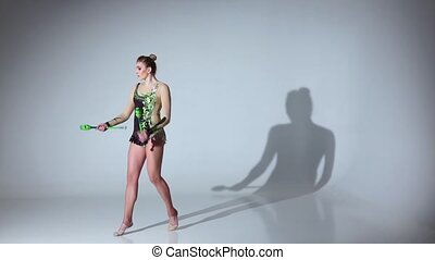 Gymnast doing back flips and standing on one leg. White background. Slow motion