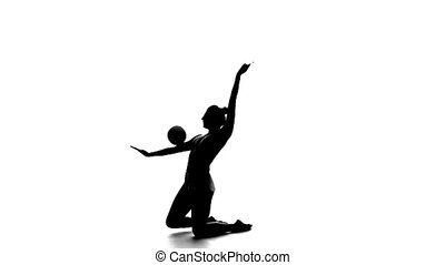 Gymnast throws the ball upwards and catches him. White...