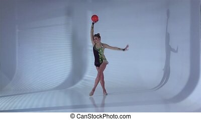 Gymnast with the ball in his hands doing acrobatic moves. White background. Slow motion