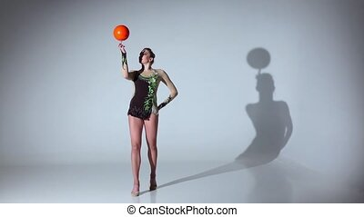 Gymnast professional spinning a ball on one finger. White...