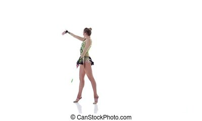 Girl gymnast with mace in hand revolve around him. White...