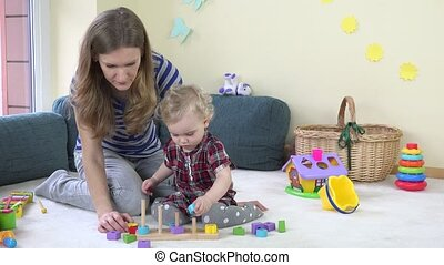 toddler girl with her mother play pull wooden colorful bricks on poles at home.