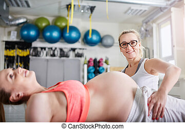 Happy personal trainer holding pregnant woman