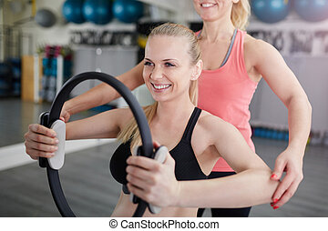 Happy woman at gym training with pilates ring