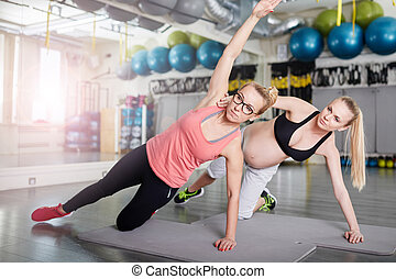 Pregnant woman doing stretching exercises with personal coach