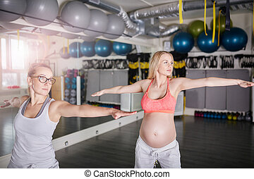 Pregnant woman training yoga stretching exercises with personal coach