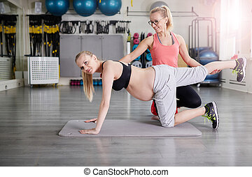 Pregnant woman training with personal coach stretching body