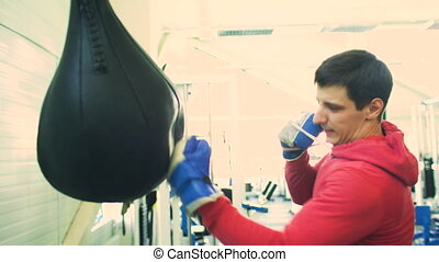 Young boxer man practicing on a punching bag in sport...