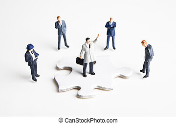 figurines and puzzle pieces - Businessmen figurines and...