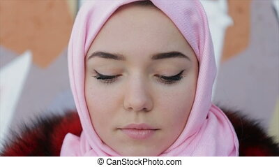 Muslim woman with her head covered with pink scarf -...