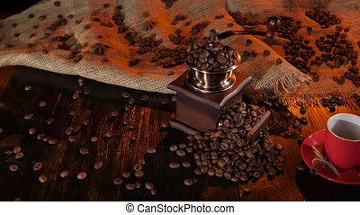 Table with a coffee grinder full of with coffee beans -...