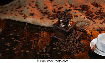 Wooden table with coffee mill full of with coffee beans,...