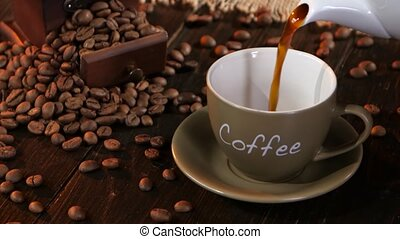 Coffee in small cup on a saucer on wooden table, pour drink...